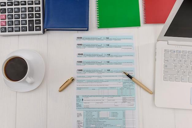 ペンとコーヒーとオフィスのテーブルで1040フォーム