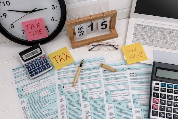 1040 form with calculator, laptop, calendar on desk