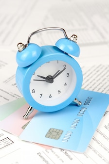 1040 individual income tax return form and blue alarm clock on credit card