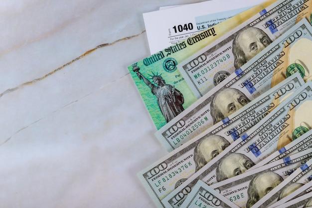 1040米国の個人所得税申告書、stimulus経済税申告書チェック、および米国通貨100米ドル紙幣