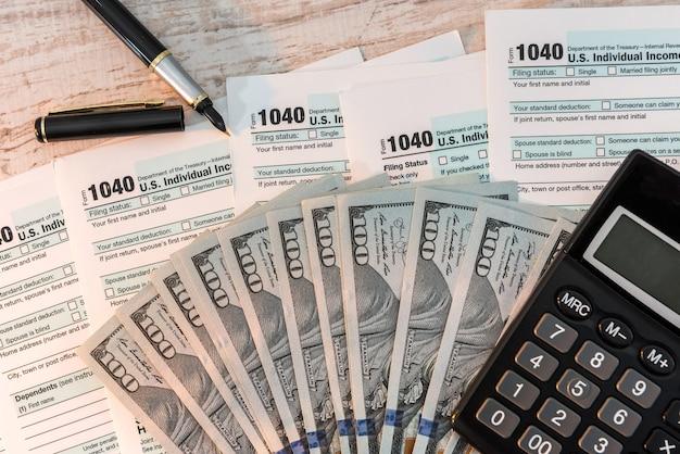 ペン計算機と米ドルを備えた机の上の1040納税申告書。ビジネスコンセプト