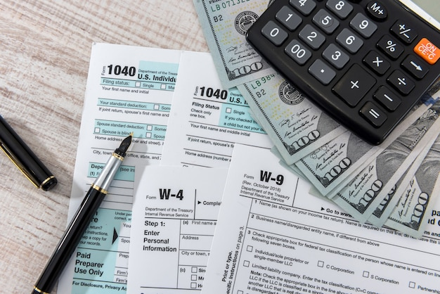 Налоговая форма 1040 на столе с ручным калькулятором и долларом сша. бизнес-концепция.