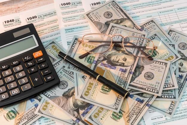 ペン計算機と米ドルを備えた机の上の1040税務フォーム。ビジネスコンセプト。