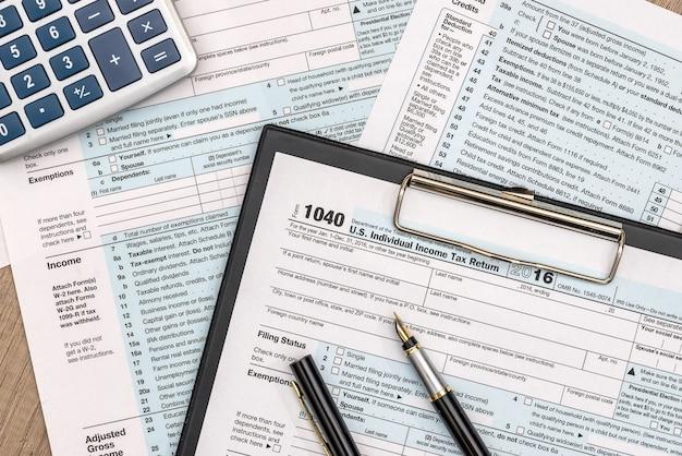 Налоговая форма 1040 на деревянном столе с ручкой и калькулятором
