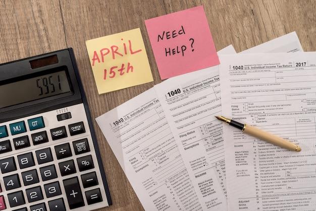 電卓、ペン、「ヘルプが必要」のテキストを含む1040税務フォーム