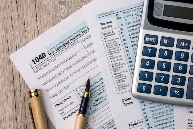 1040 tax form with calculator and pen