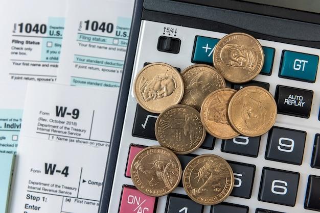 コインと電卓を備えた1040税務フォーム。課税時間、概念