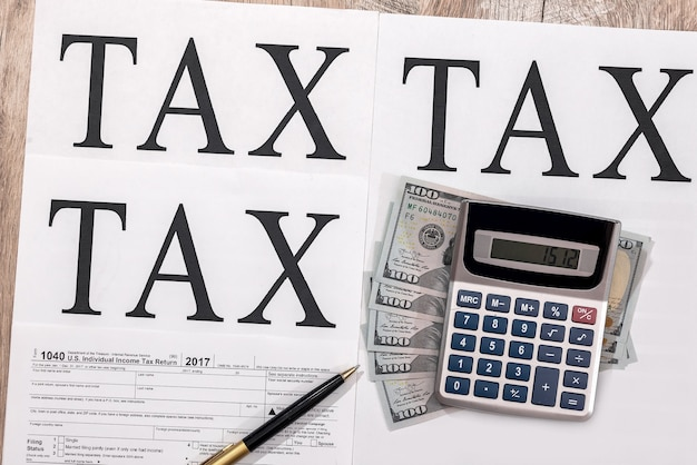 1040 tax form with dollars, calculator and pen