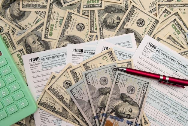 ペンと米ドルの請求書、財務概念を含む1040税務フォーム