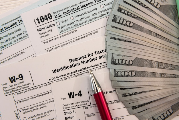 1040 tax form with pen and us dollar bills, financial concept
