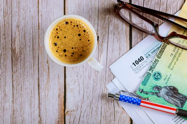 1040 tax forms top view with coffee cup and refund check, pencil with glasses