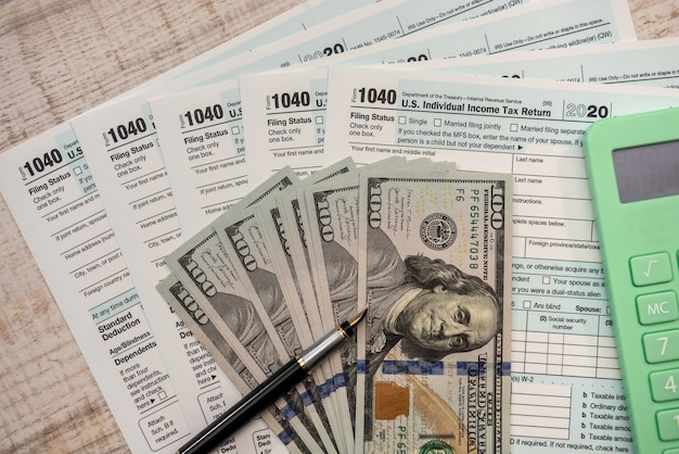 Налоговая форма 1040 сша с ручкой и долларами на столе. расчет возврата налога