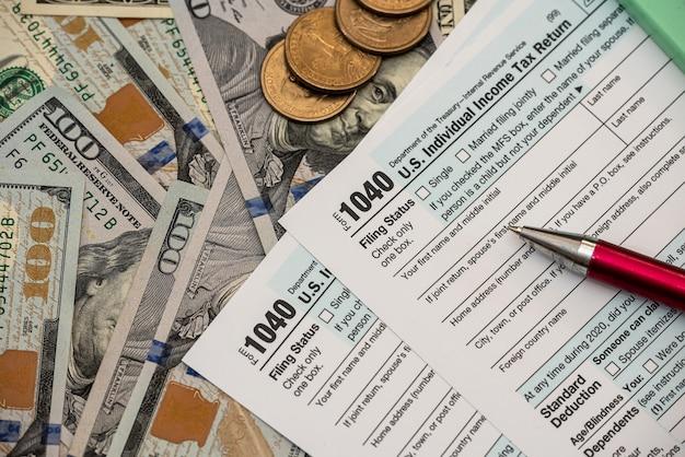 Налоговая форма 1040 сша с ручкой и долларами на столе