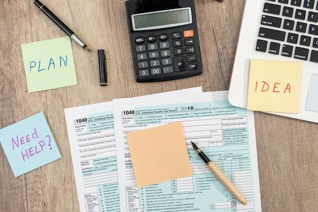 ラップトップコンピューターのメモ帳、ペン、テーブルのステッカー、オフィスの職場を備えた1040usa個人納税申告書。税の概念