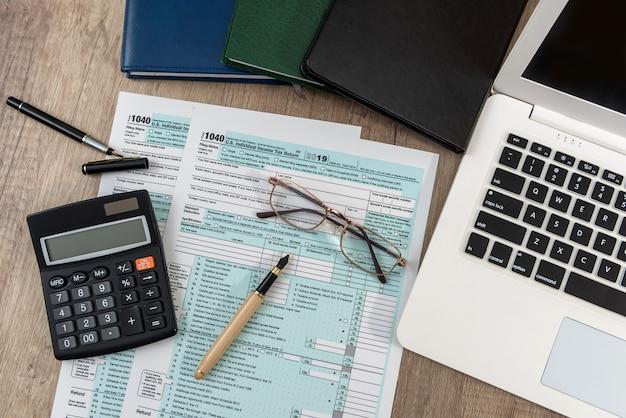 노트북 컴퓨터 메모장, 펜, 스티커 테이블, 사무실 직장 1040 미국 개인 세금 양식. 세금 개념.