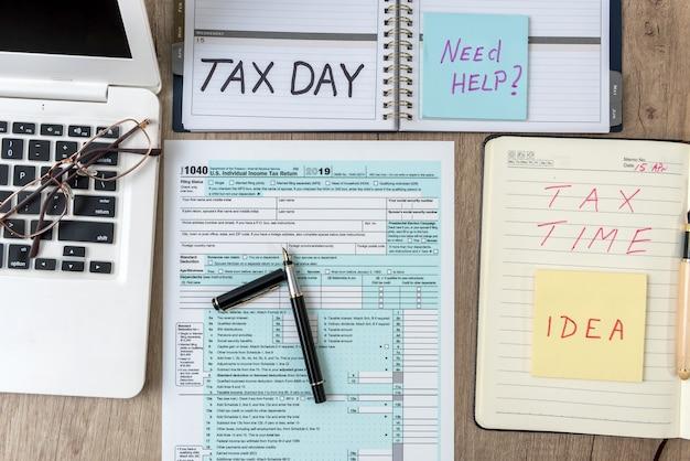 ラップトップコンピューターのメモ帳、ペン、テーブルのステッカー、オフィスの職場で1040米国個人税フォーム。税の概念。