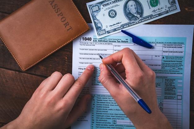 米国の税務フォームに記入します。税務フォーム1040、パスポート、木製のテーブルにお金。金融の概念、税の概念。個人所得税申告。納税時期