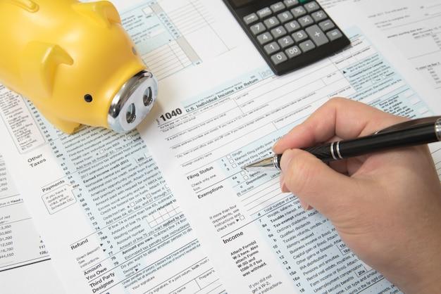 米国納税申告書1040、貯金箱、電卓、ペン。