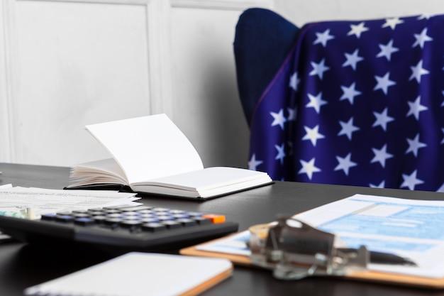 Налоговая концепция - 1040 налоговых форм, ручка, деньги и флаг