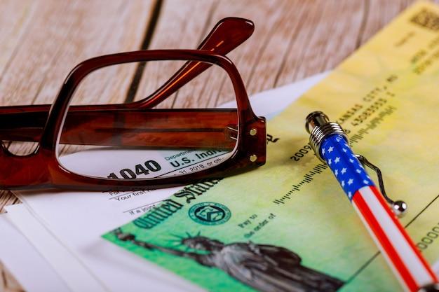 ペン作業机に眼鏡を掛けた米国個人所得税申告書1040フォーム