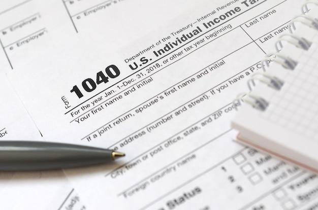 Ручка и блокнот лежит на налоговой форме 1040