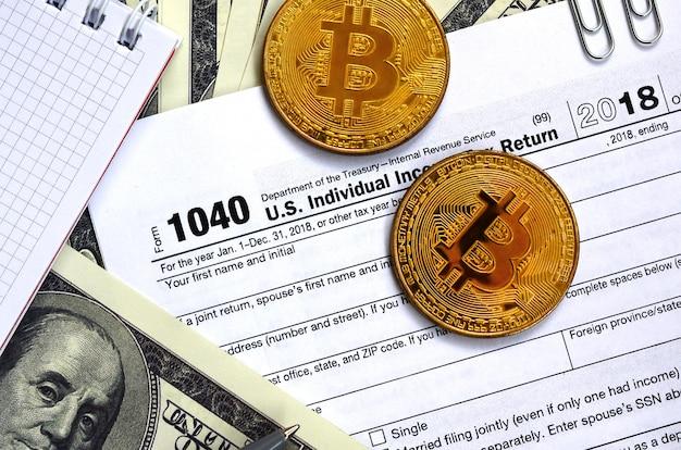 ペン、ビットコイン、およびドル紙幣は、1040年米国個人所得税申告書に記載されています。税金を払う時間