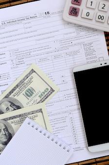 1040納税申告書に記載されている品目の構成。ドル紙幣、電卓、スマートフォン、ペーパークリップ、メモ帳。税金を払う時間