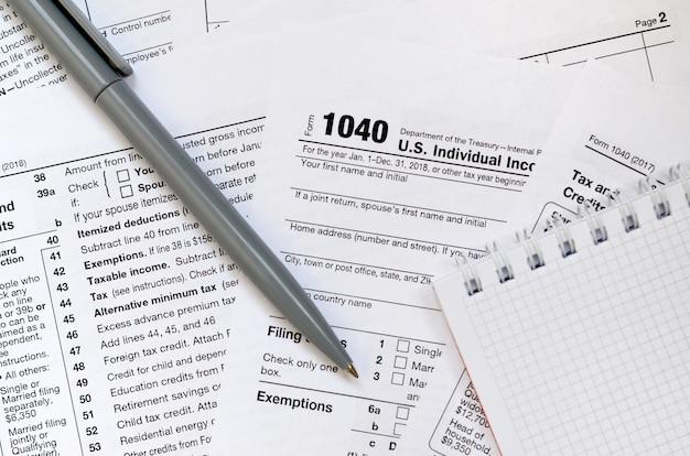 Ручка и блокнот лежат в налоговой форме 1040 индивидуальная налоговая декларация сша. время платить налоги