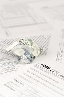 1040 форма декларации о подоходном налоге с физических лиц и скомканная стодолларовая купюра