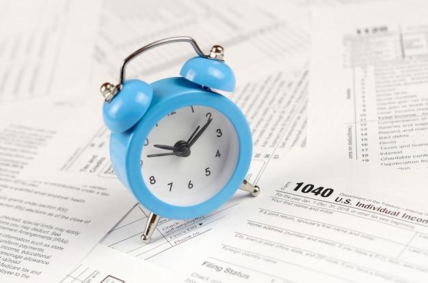 1040個人所得税申告書と青い目覚まし時計