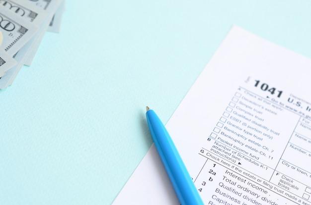 1041納税申告書は100ドル紙幣と青いペンの上にあります