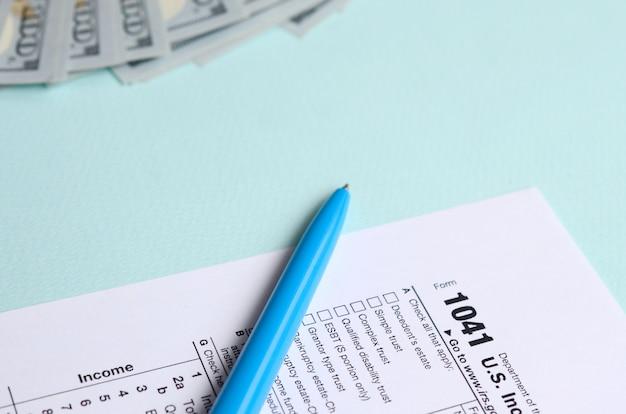 1041 tax form lies near hundred dollar bills and blue pen on a light blue
