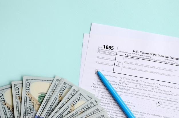 1065 tax form lies near hundred dollar bills and blue pen on a light blue background. us return for parentship income
