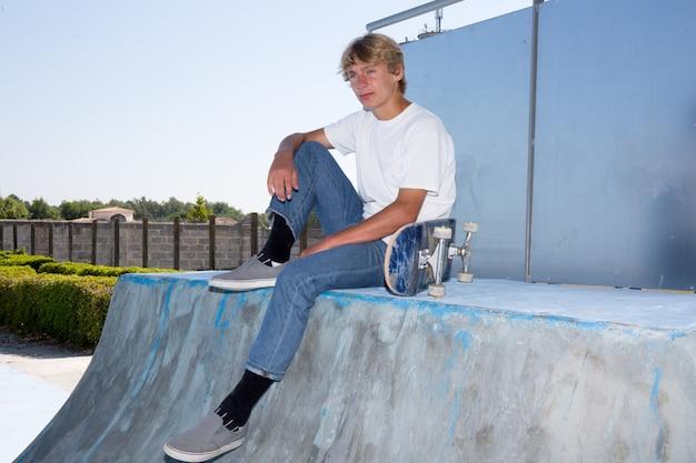 スポーツ概念図。スケートパークに座っている10代のスケートボーダー