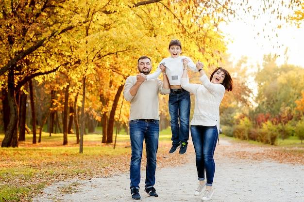 秋の公園で外出する10代の息子と幸せな家族