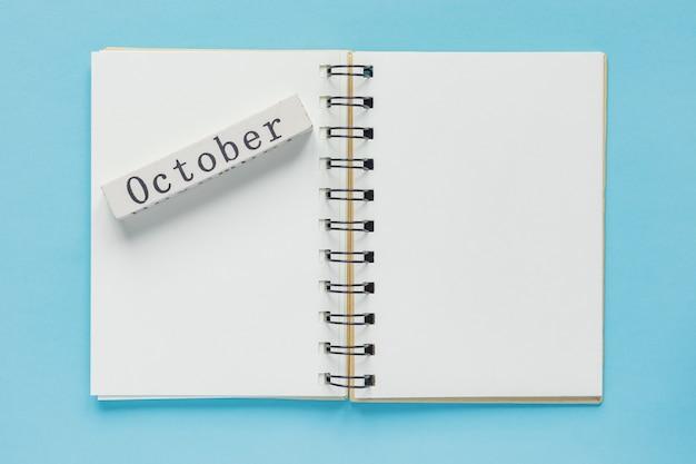 青のノートとメッセージと10月の木製カレンダーバーのきれいなスパイラルメモ帳