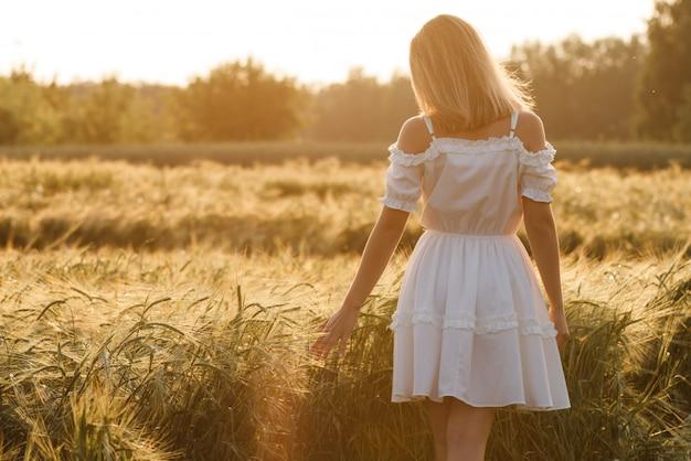 屋外を楽しむ自然の美しさの少女。春の野、太陽の光で実行されている白いドレスの美しい10代のモデルの女の子。