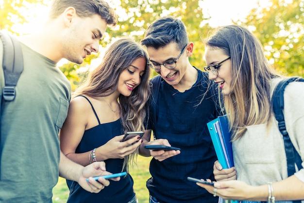 公園でのスマートフォンと友達の10代のグループ