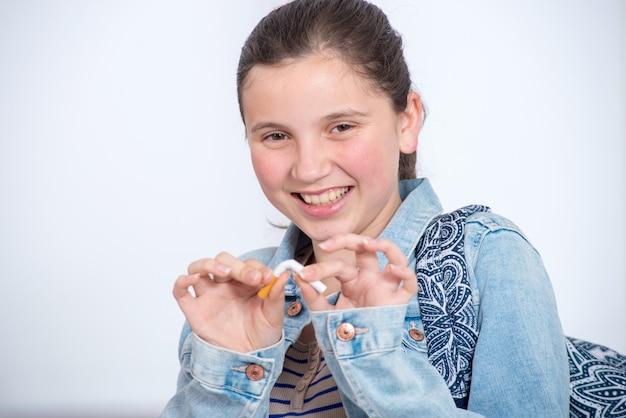 タバコを壊す幸せな若い10代の少女