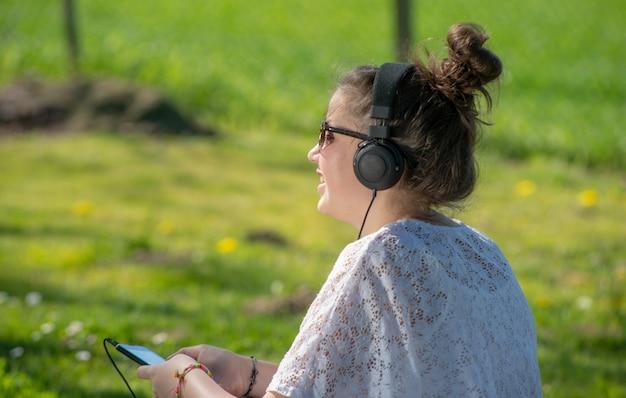 若い10代の女の子が公園でヘッドフォンで音楽を聴く