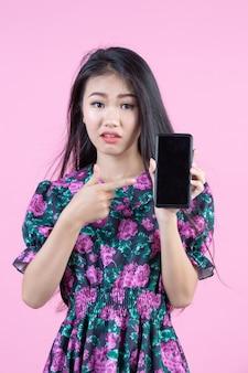 電話と顔の感情を示す10代の少女