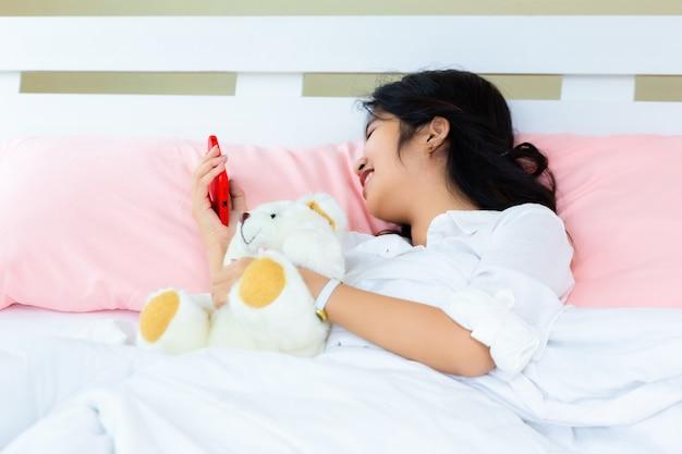 10代の女性がベッドでスマートフォンを使用します。