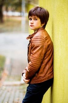 黄色の壁を背景にポーズ少年10代