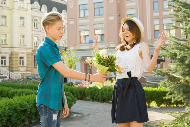 10代の少年は彼のガールフレンドに花の花束を与える