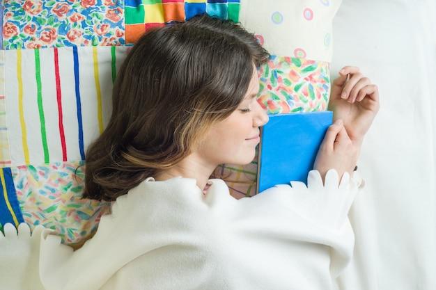 枕の上の本で眠っている10代の少女のクローズアップ