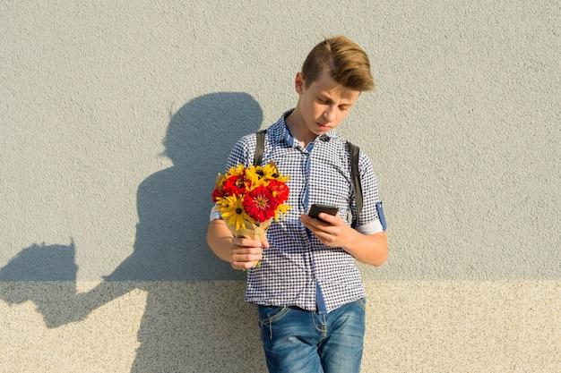 花の花束と10代の少年の屋外のポートレート