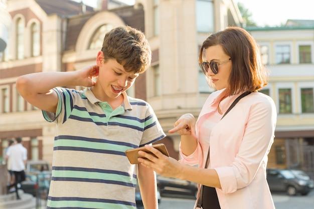 10代の母と息子が携帯電話を見ています。