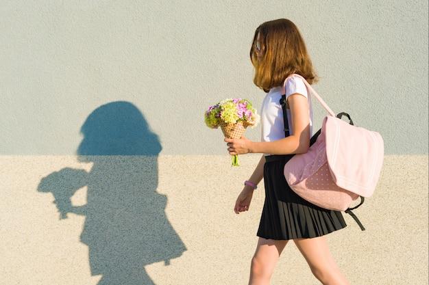 学校に戻る。幸せな10代の少女の屋外のポートレート