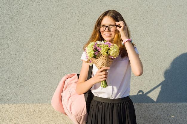 メガネをかけて花束を持つ10代の少女
