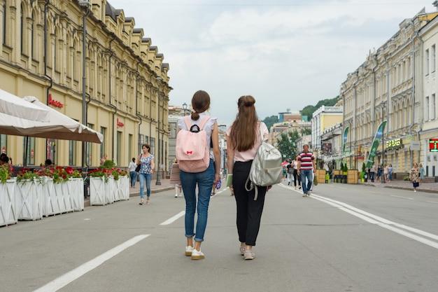 若い10代の女子学生が通りを歩いています。